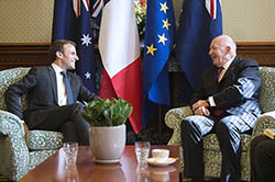 President Macron meets with the Governor-General of Australia. In the background are the flags of Australia, France and the European Union.