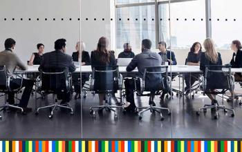 A group of eleven people wearing business clothes sit around a long rectangular table. They are talking to each other.