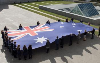Image of schoolchildren holding the flag on top of Parliament House