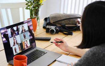 Women having a video conference on her laptop, which is sitting on a table next to a mug, handbag and camera