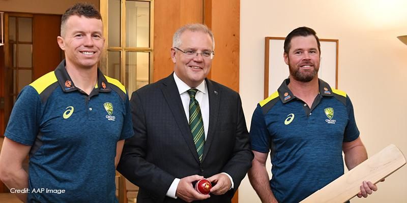 Three men stand in a room. In the background is a white wall and a doorway through to neighbouring room. The man on the left wears a blue polo shirt and blue jeans. The man in the middle wears a dark suit. The man on the right wears darks trousers and a blue shirt. He holds a cricket bat.