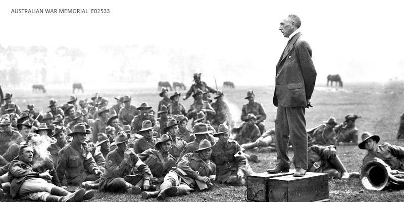Former Australian Prime Minister, Right Honourable William Morris (Billy) Hughes (standing on four ammunition boxes), addressing Australian soldiers, one and a half miles from Amiens, France in 1918.