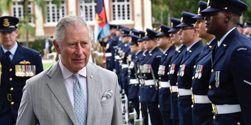 The Prince of Wales in grey suit walks along a line of officers in blue uniforms and holding guns. In the background is a building.