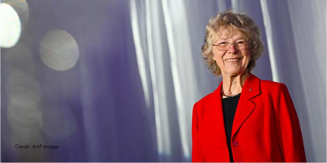 A woman wearing a bright red jacket is standing in front of a curtain. She is wearing gold glasses with a gold chain.