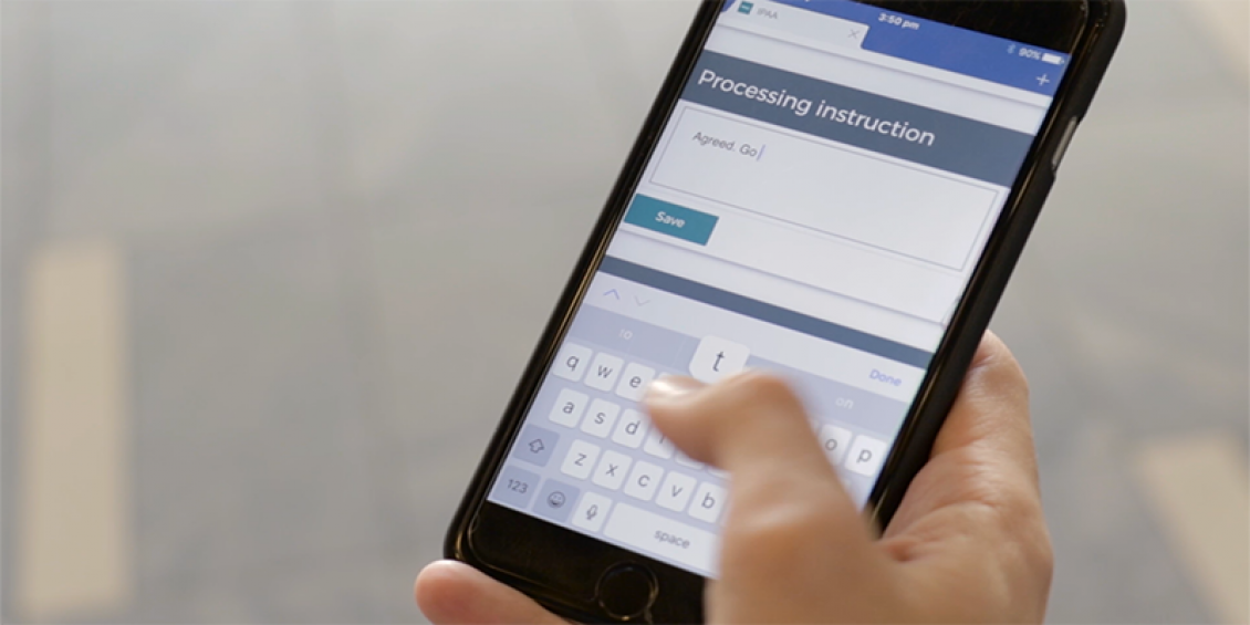 A human hand holding a generic smart phone, entering the letter T into a web application.