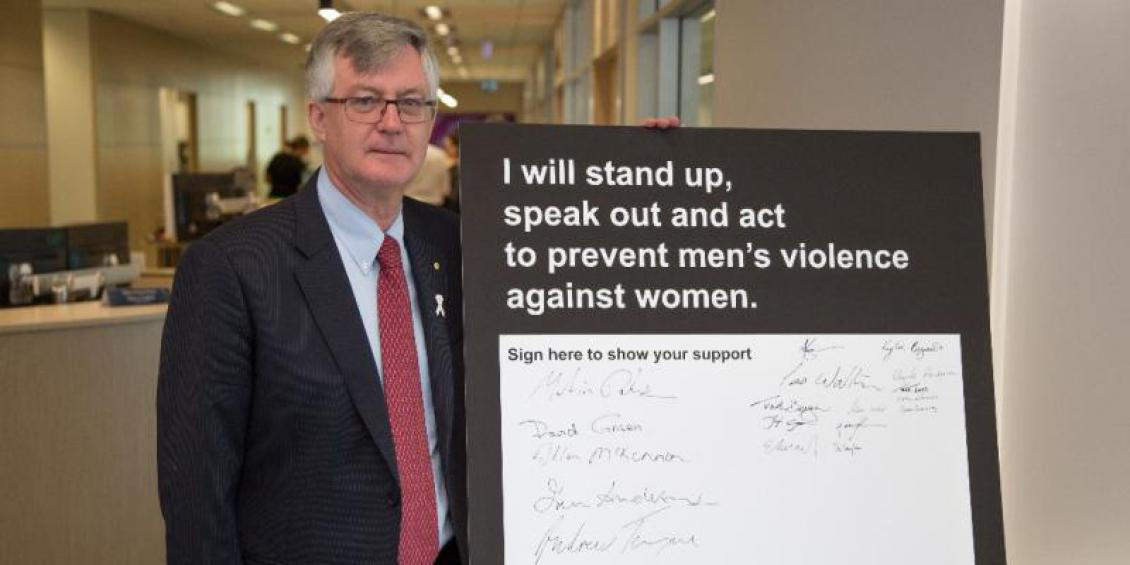 Dr Martin Parkinson AC PSM, signs the White Ribbon pledge board that will be available for staff to sign in the lead up to White Ribbon Day.
