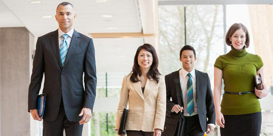 Two women and two men walk through an office.