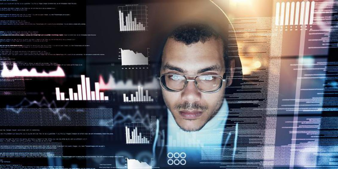 A man wearing glasses looking into a digital interface of charts and numbers.