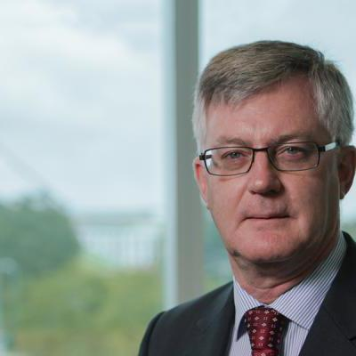 A photo of Martin Parkinson, parliament house visible in the background.